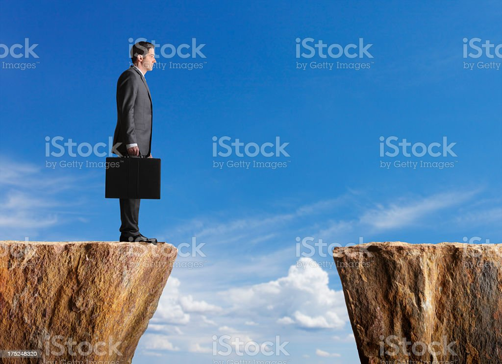 Business standing at edge of cliff looking towards other side stock photo