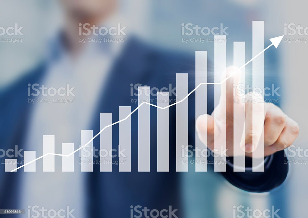 Business success with growing, rising charts and businessman in background stock photo