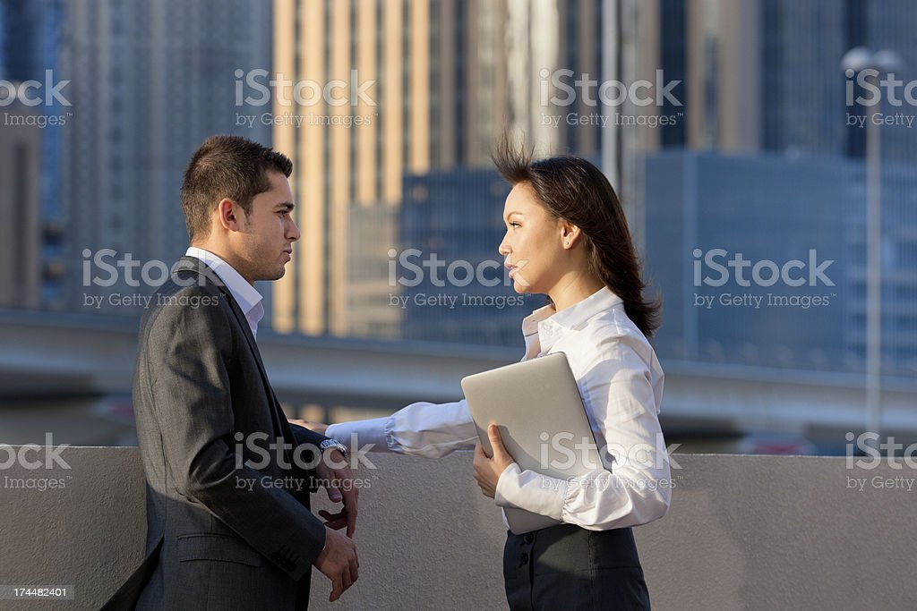 business talk between businesswoman and man in financial district stock photo