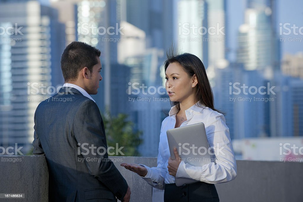 business talk of businessman and woman holding laptop in Dubai royalty-free stock photo