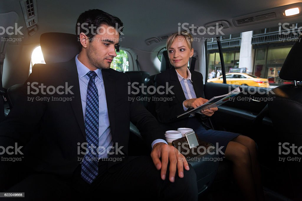 Business team analyzes report in exectuive car stock photo