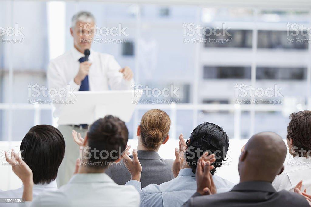 Business team applauding a mature businessman stock photo