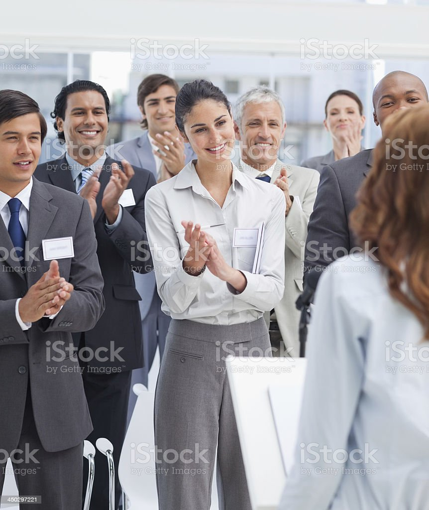 Business team applauding a woman while standing stock photo