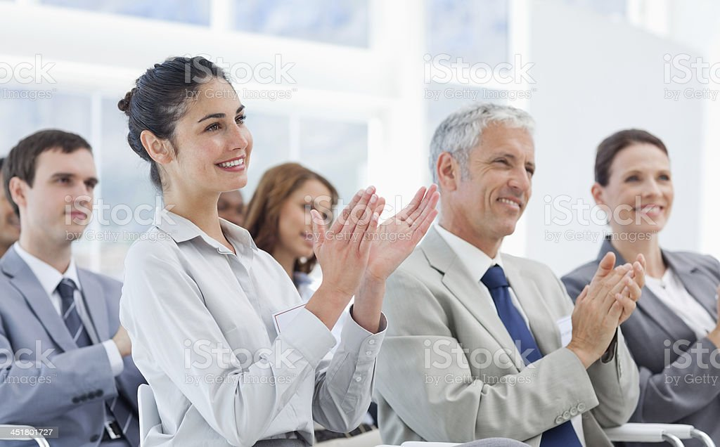 Business team applauding while looking ahead stock photo