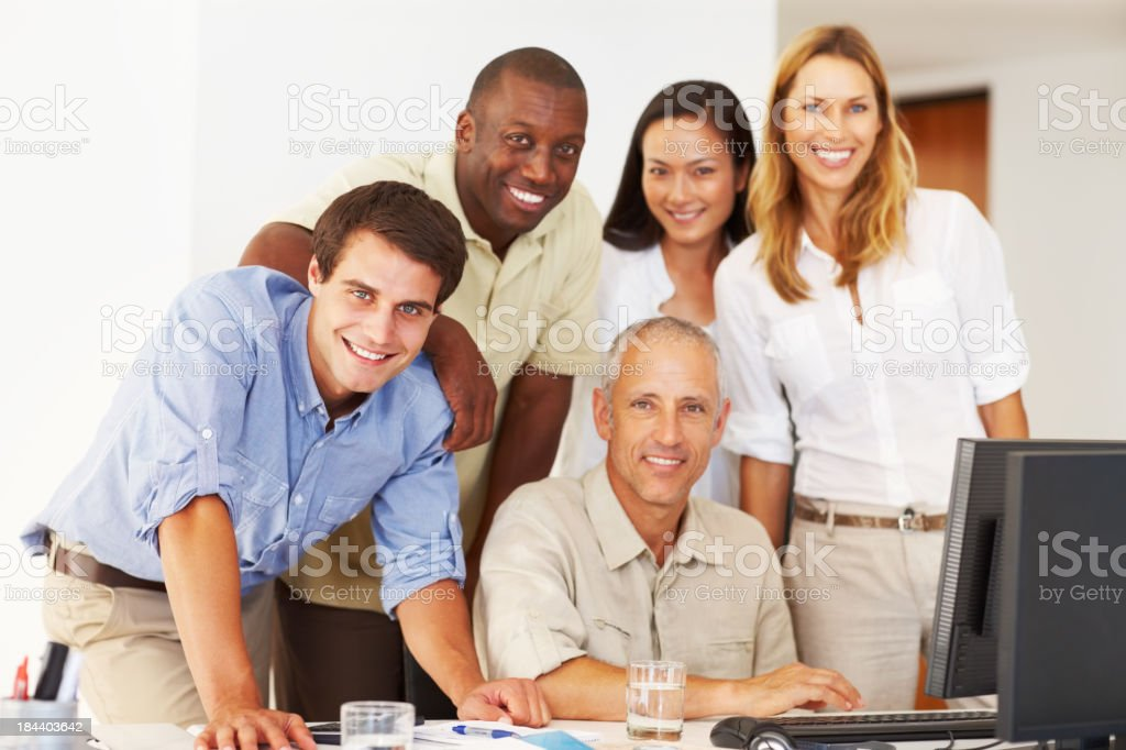 Business team around a computer, smiling and working royalty-free stock photo
