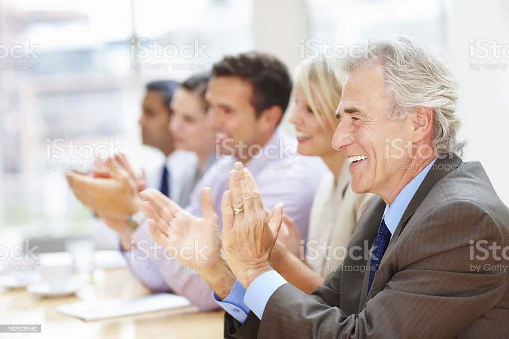 Business team clapping hands in meeting royalty-free stock photo