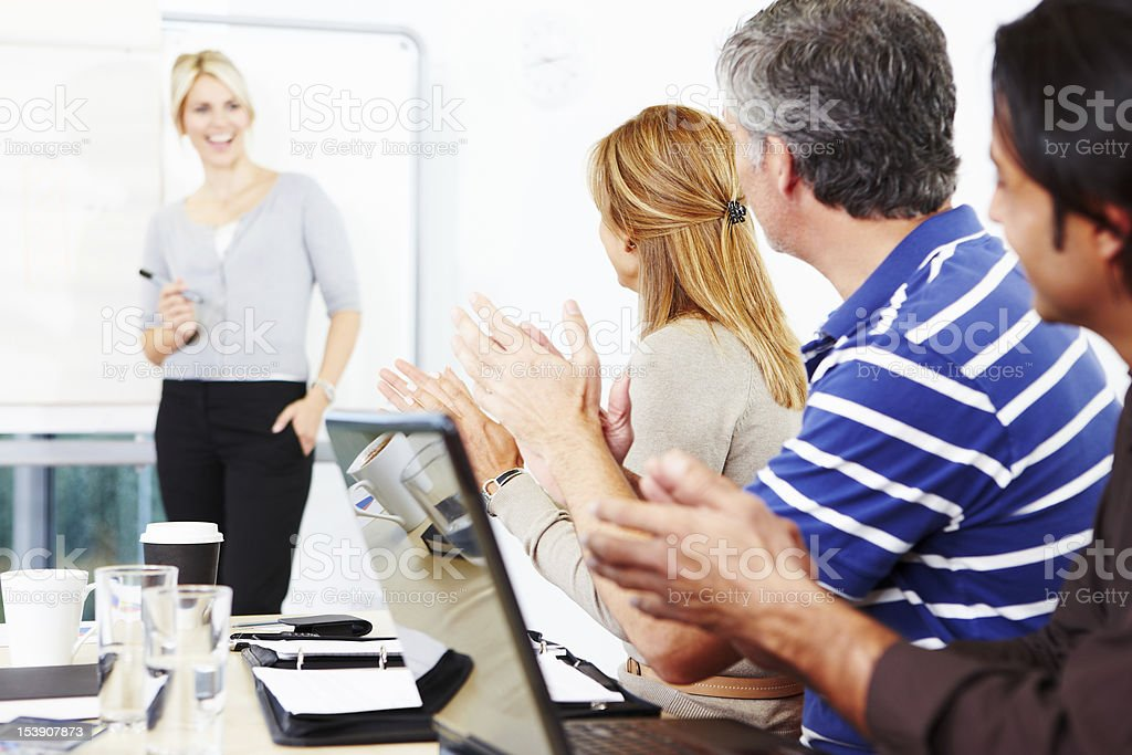 Business team clapping young woman giving presentation royalty-free stock photo