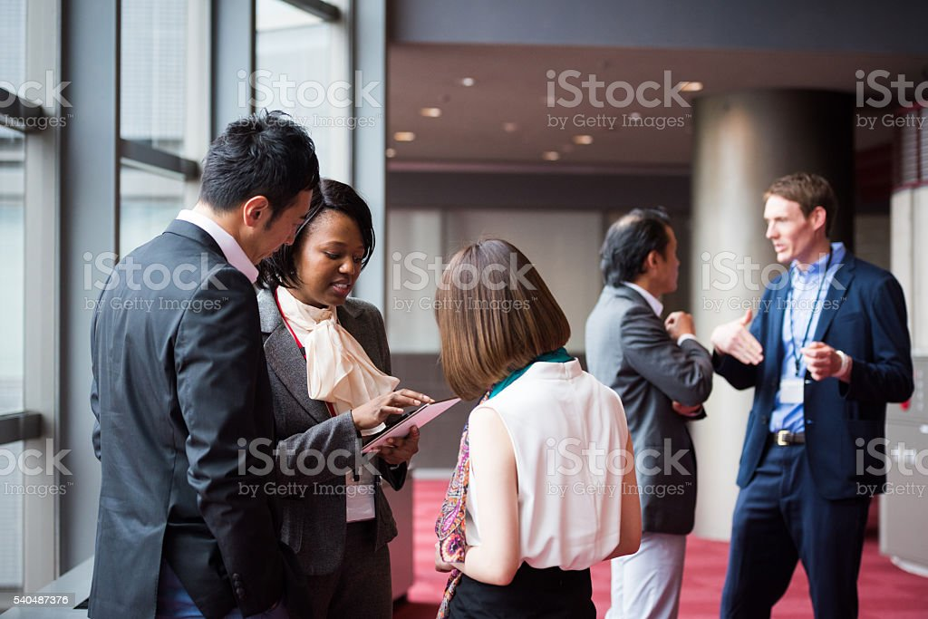 Multi ethnic business team consultng during a break at a conference