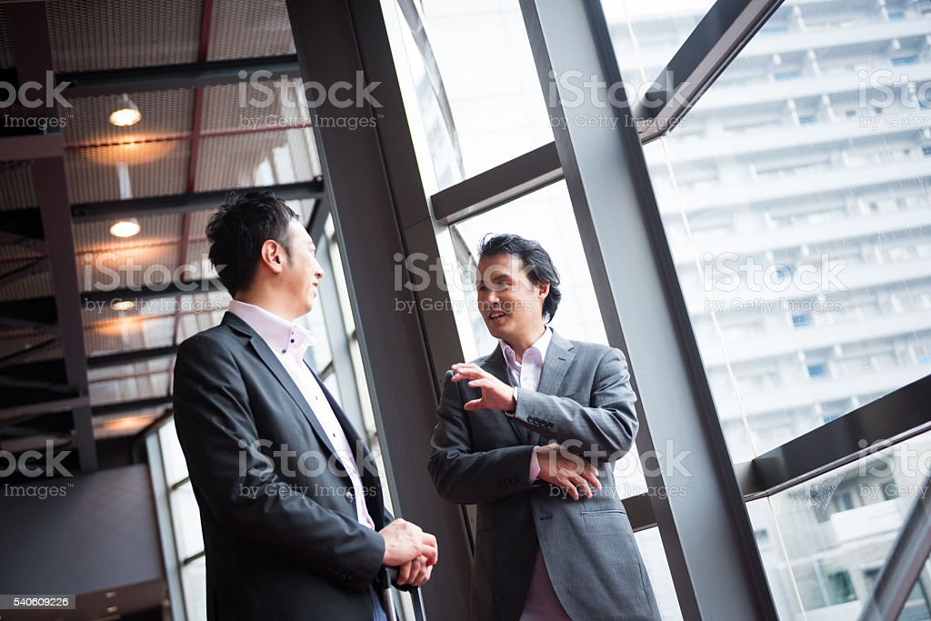 Asian bsuinessmen consulting in a conference foyer