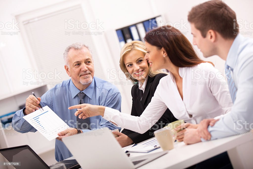 Business team cooperating while working on a diagram at office. stock photo
