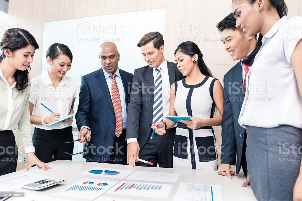 Business team discussing graphs and numbers in meeting stock photo