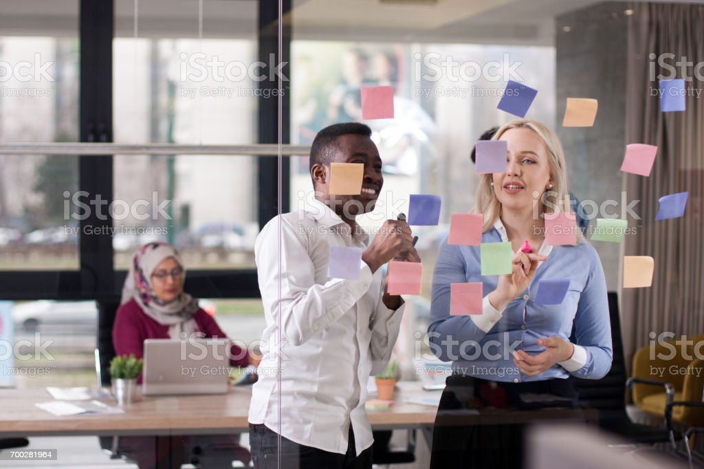 Business team discussing ideas on glass wall with sticky notes stock photo