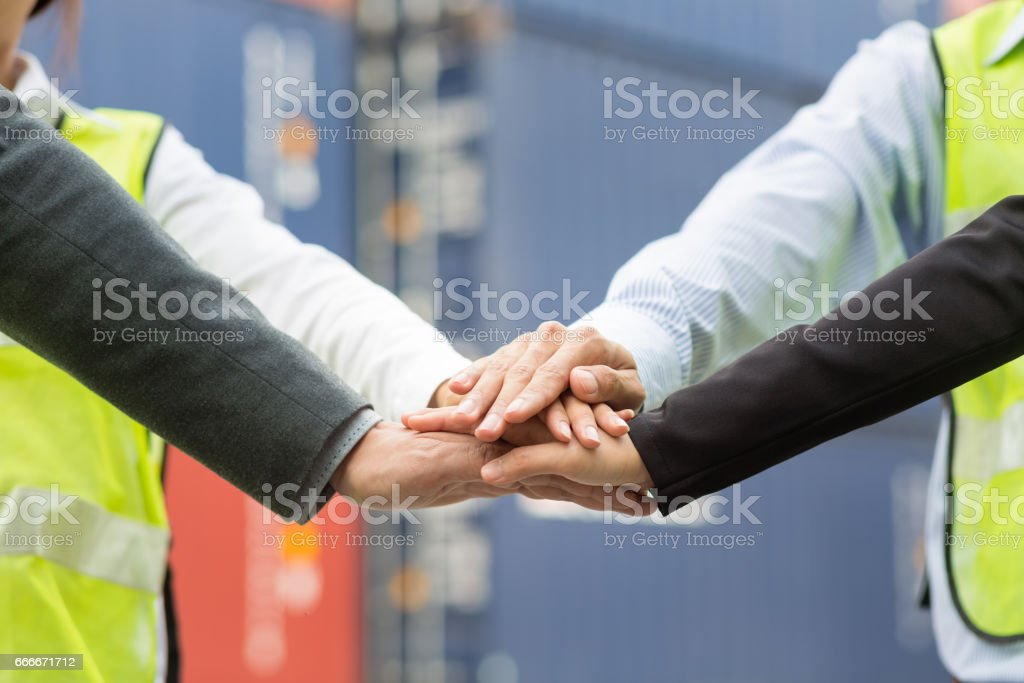 Business team in logistic industry join hand for collaboration after project achieve with container cargo for export and import in background. Teamwork concept stock photo