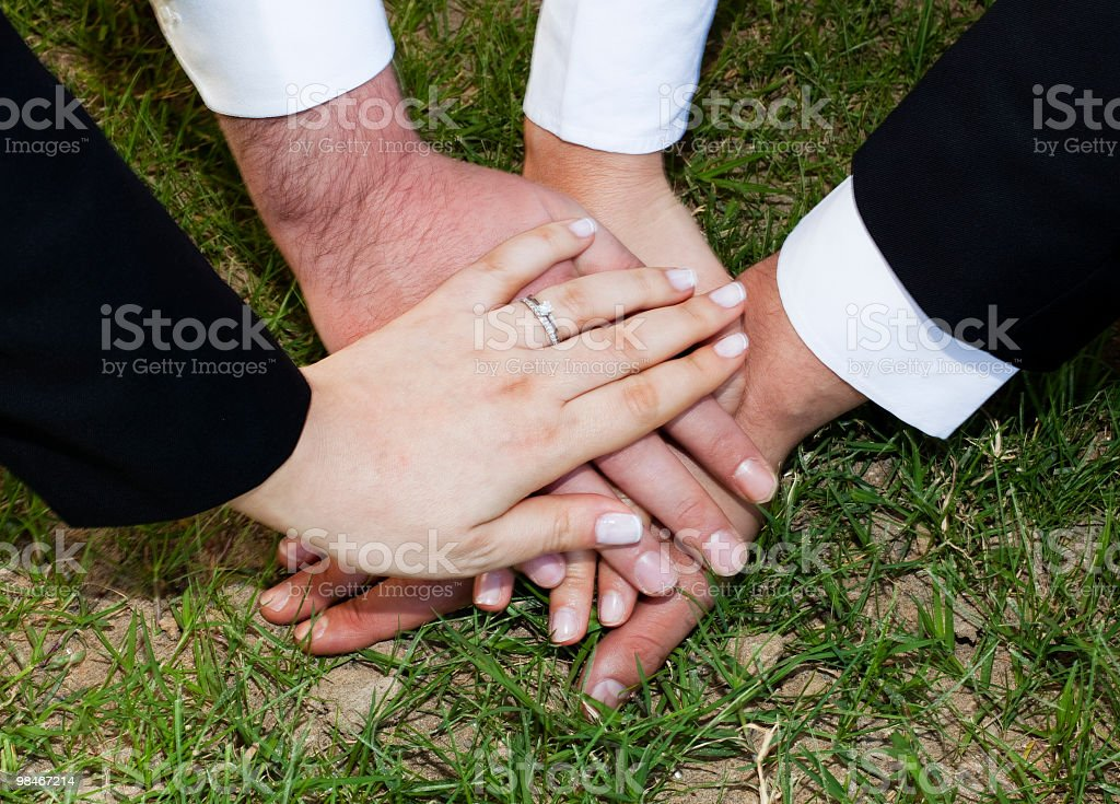 Business team joining hands on Grass stock photo