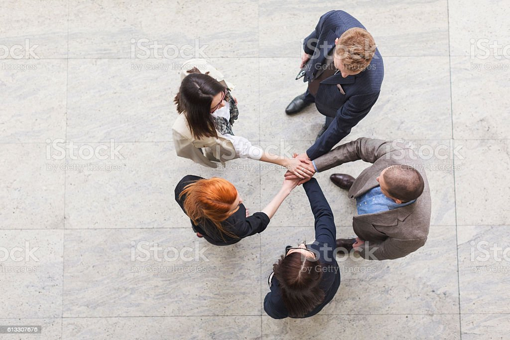 Business team joyning hands high angle view stock photo