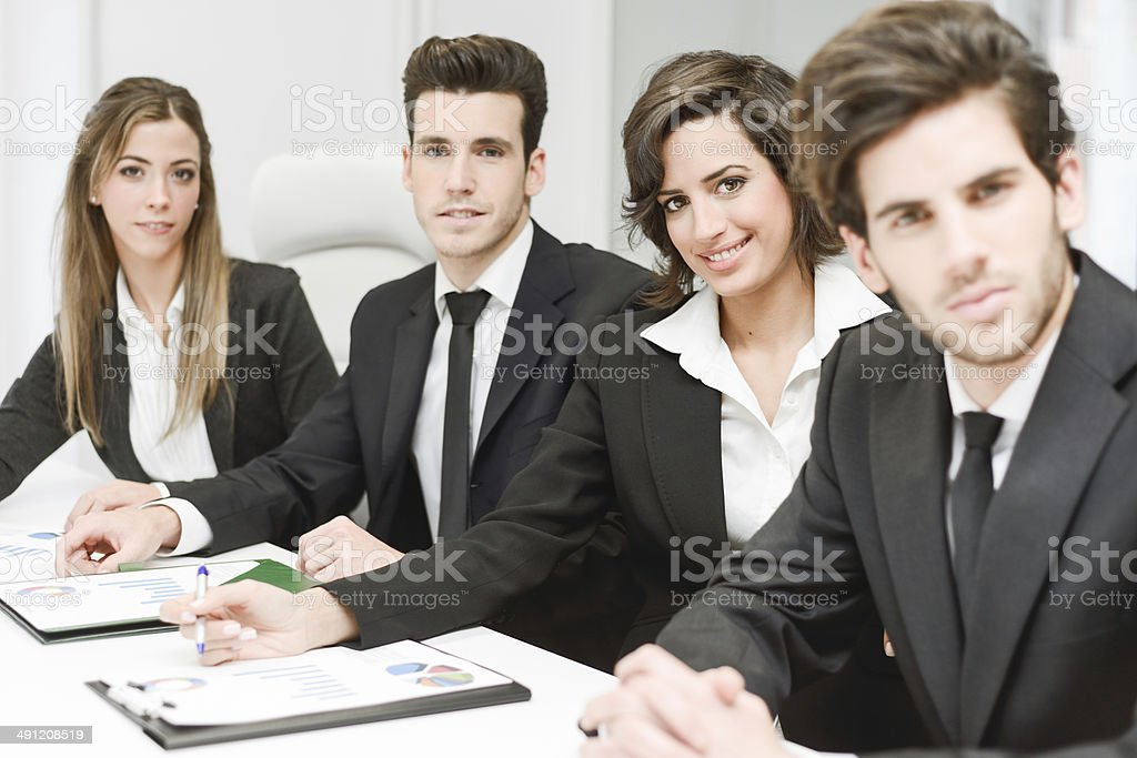 Business team looking at camera in working environment stock photo
