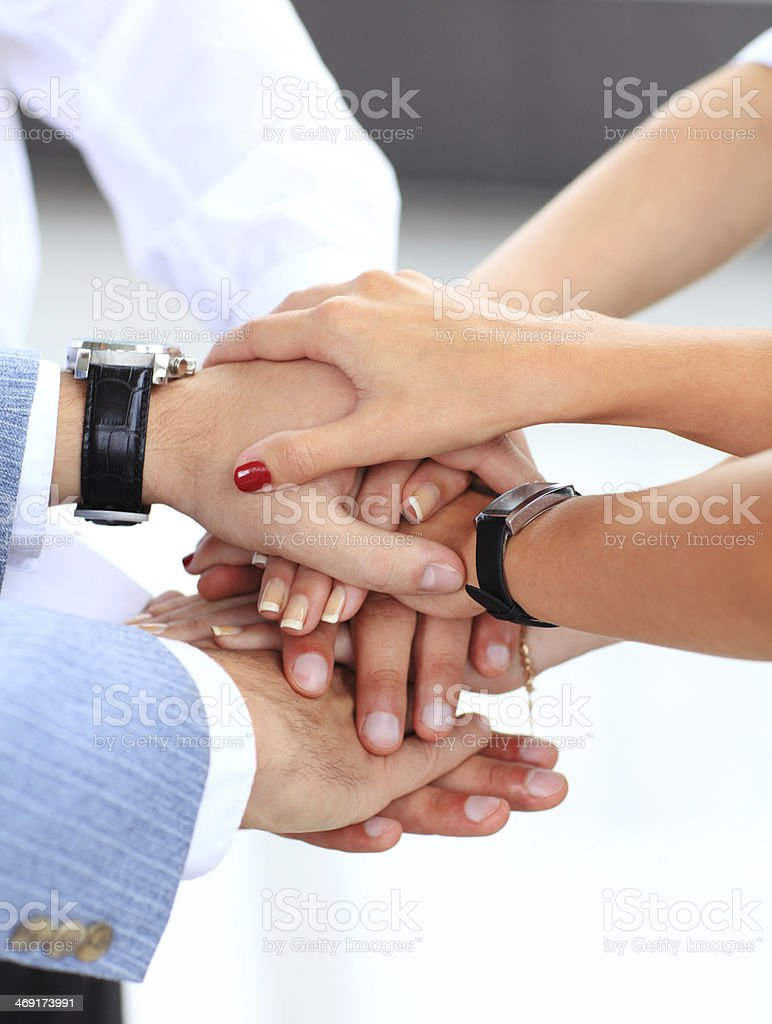 business team putting their hands on top of each other stock photo