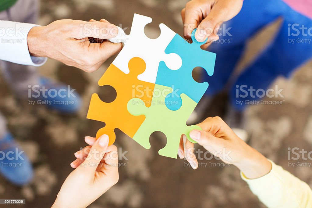 Business Team Solving Puzzle In Office stock photo