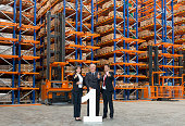 Business team standing behind large number 1 in warehouse