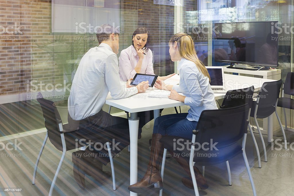 Business team studying a tablet PC at meeting stock photo