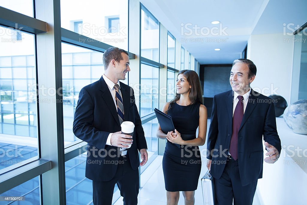 Business team walking and talking down the hall stock photo