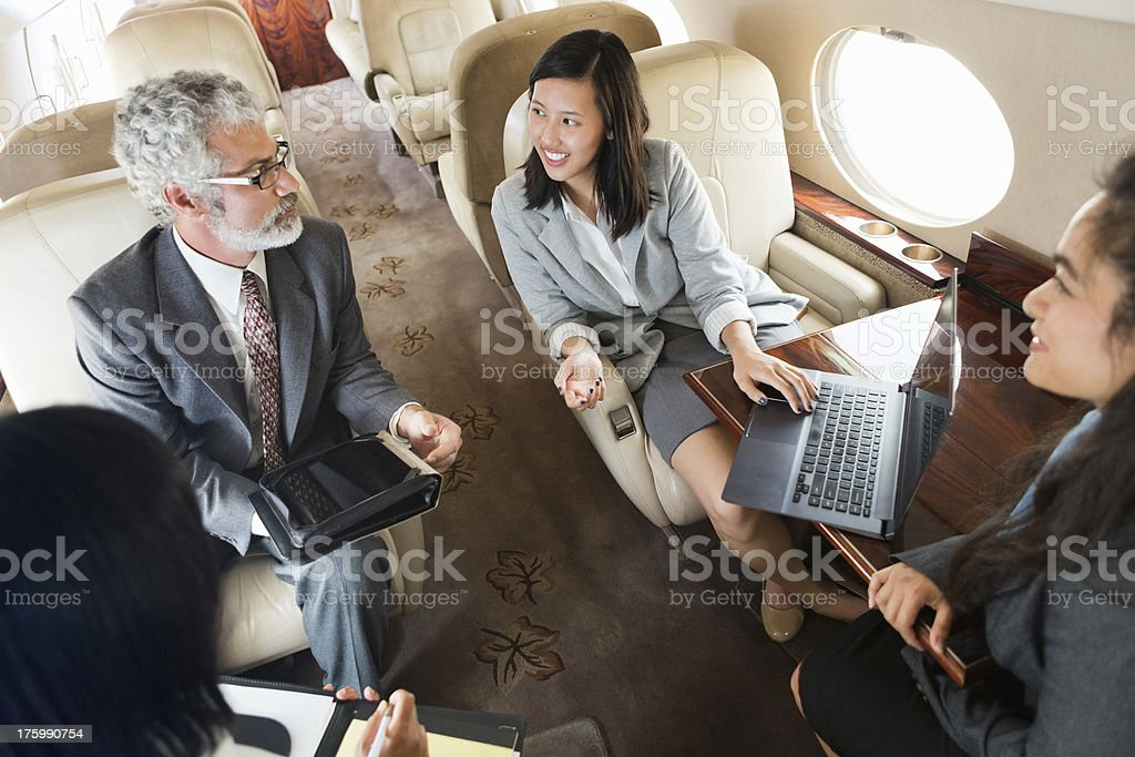 Business team working whlie travelling on corporate private jet stock photo