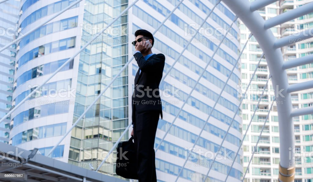 business, technology and people concept - serious businessman with smartphone talking over office building stock photo