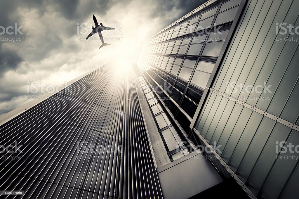 Business towers with an airplane silhouette stock photo