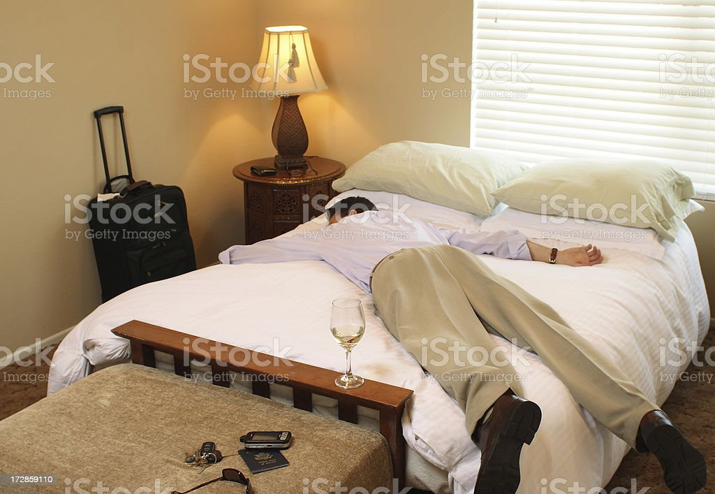 Business Traveler Asleep on Bed stock photo