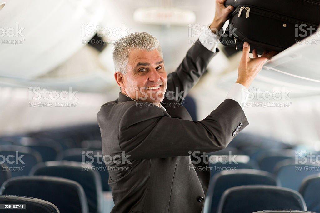 business traveler putting luggage into overhead locker on airplane stock photo