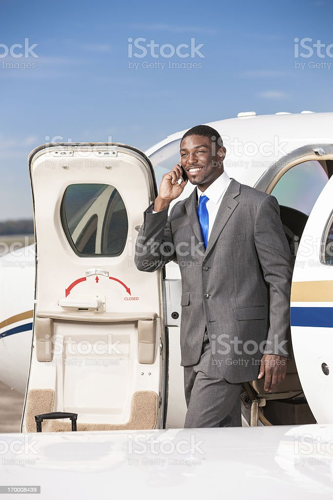 Business Traveler Talking on Cell Phone While Exiting Corporate royalty-free stock photo