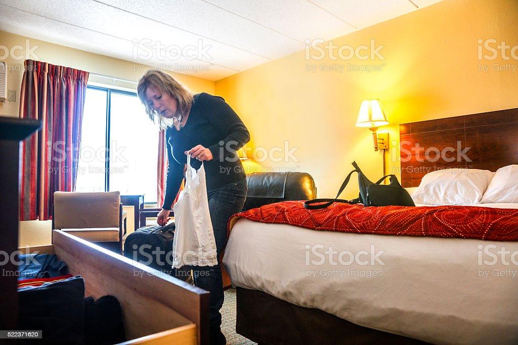 Business traveler unpacks her suitcase in hotel stock photo