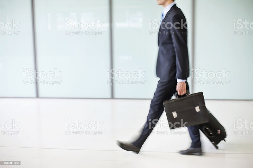 Business traveler with briefcase and pull case, side view stock photo
