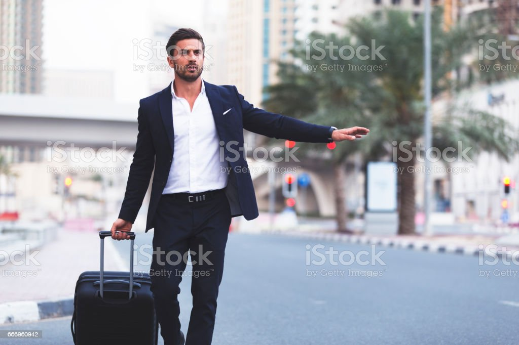 Business Traveller hailing a cab stock photo