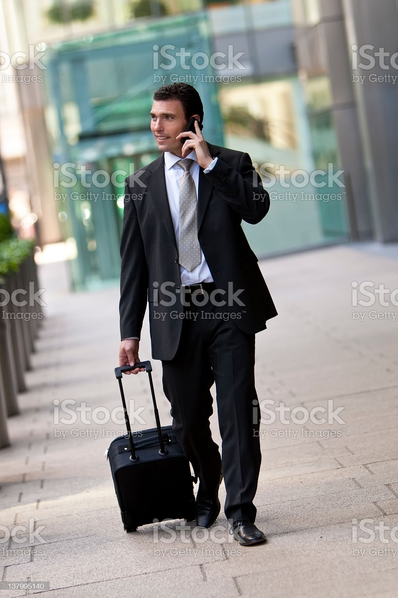 Business Traveller On His Cell Phone and Pulling Suitcase royalty-free stock photo