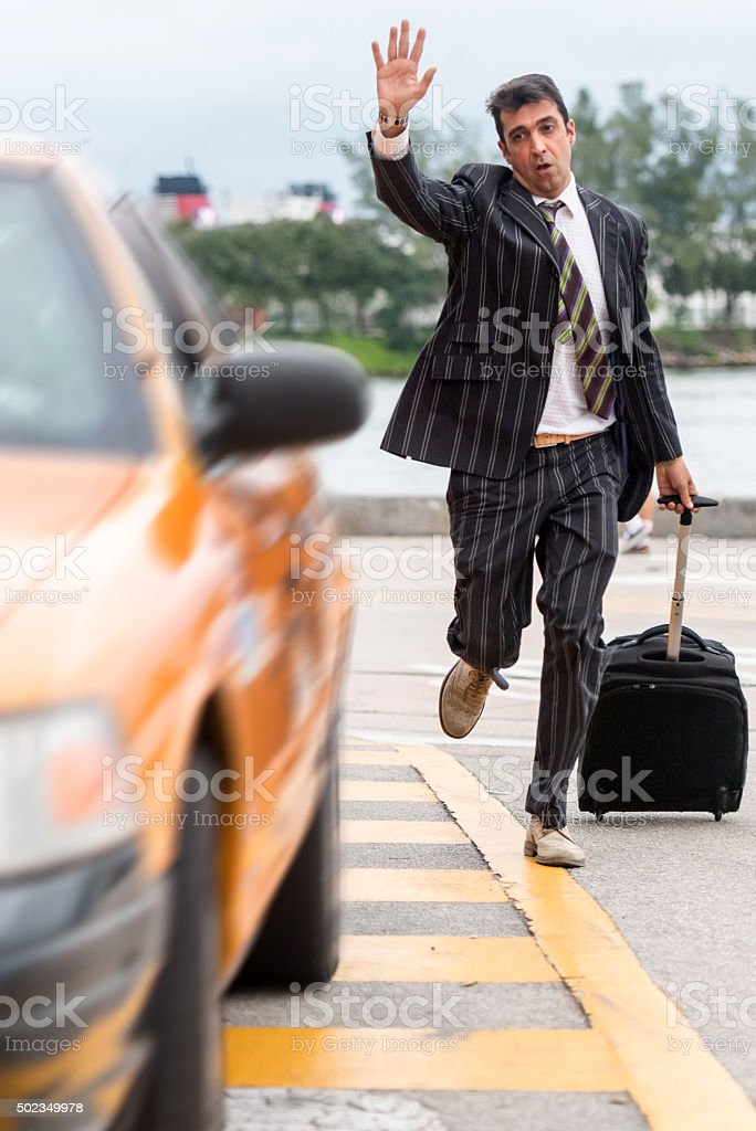 Business traveller running after a taxi cab stock photo
