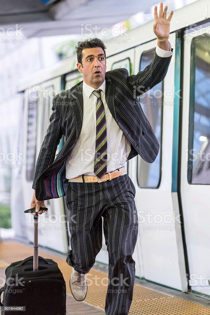 Business traveller running after a train stock photo