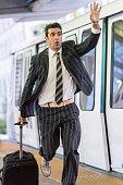 Business traveller running after a train