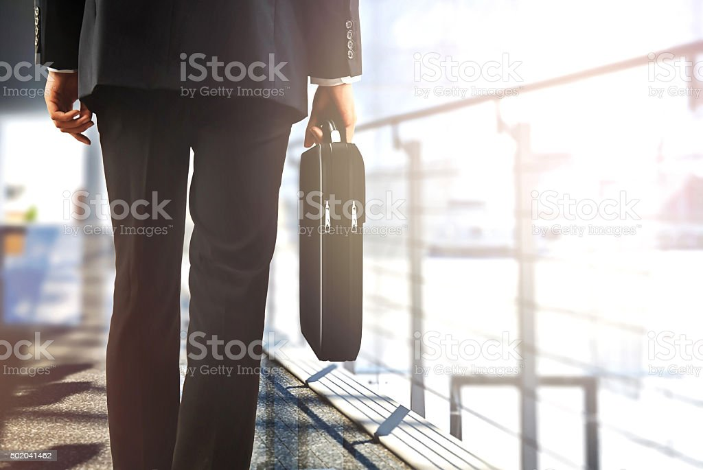 business travellers walking in airport with luggage stock photo