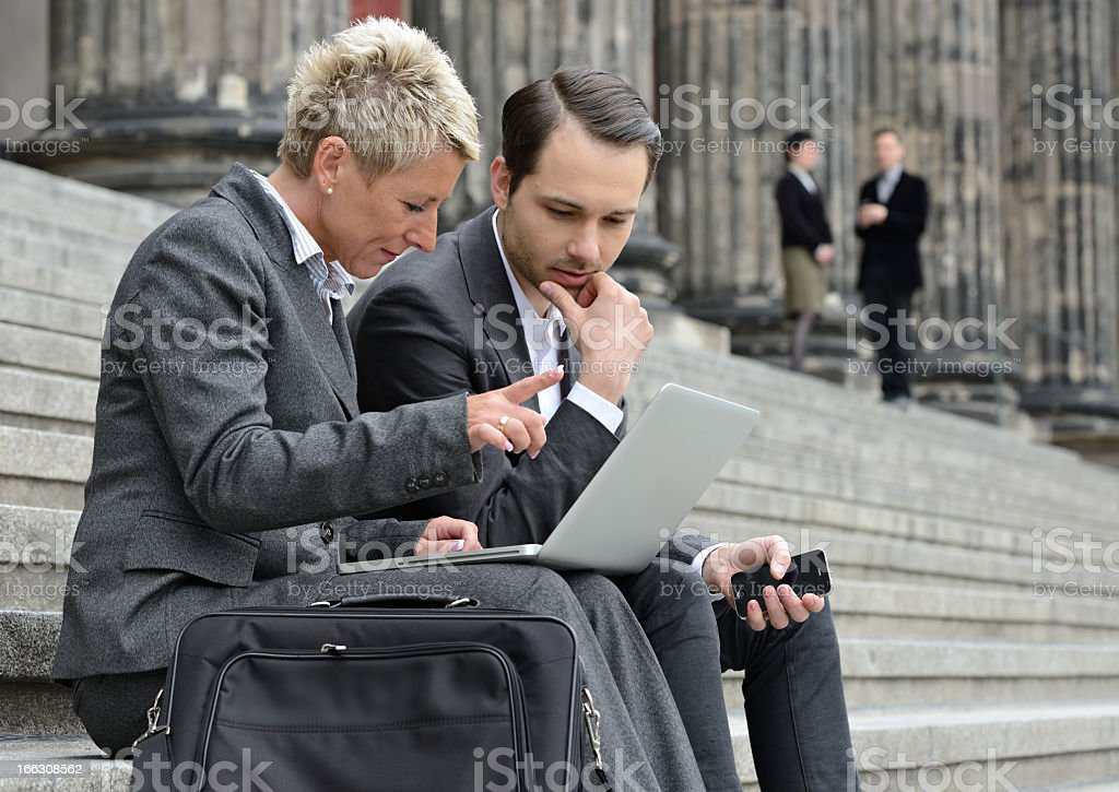 Business Woman and Man with Laptop Discussing Outdoors on Staircase stock photo