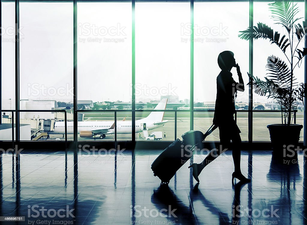 Business woman at Airport - Silhouette of a passenger stock photo