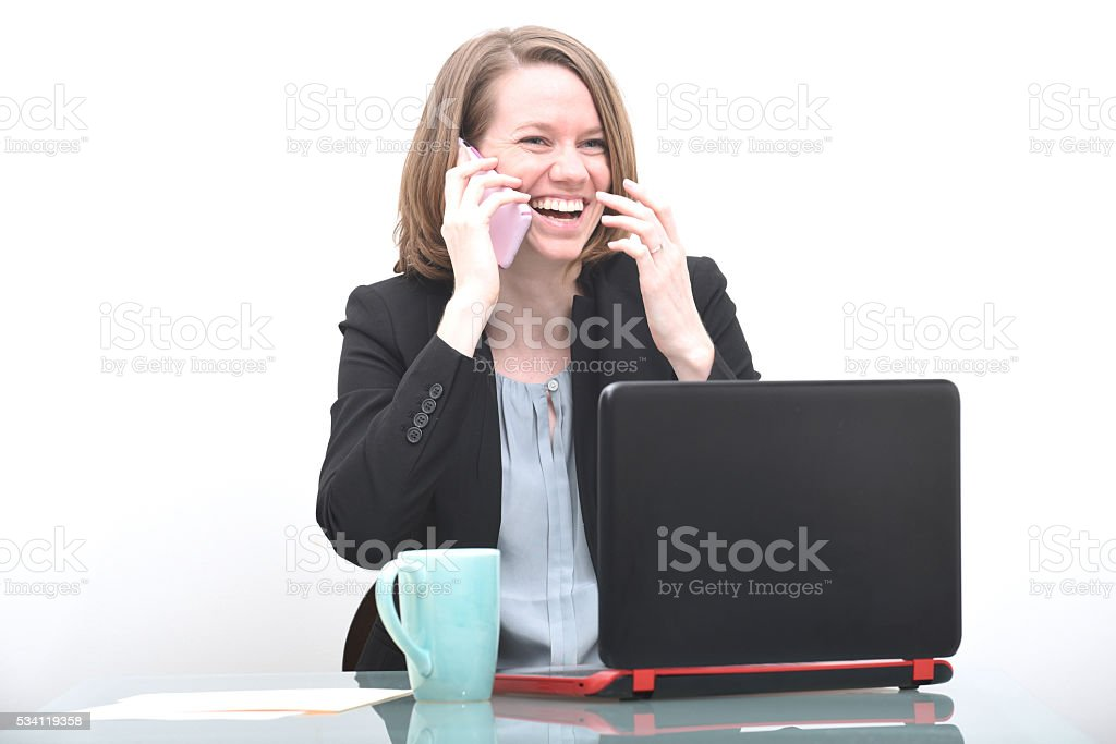 Business woman at desk laughing and talking on phone stock photo
