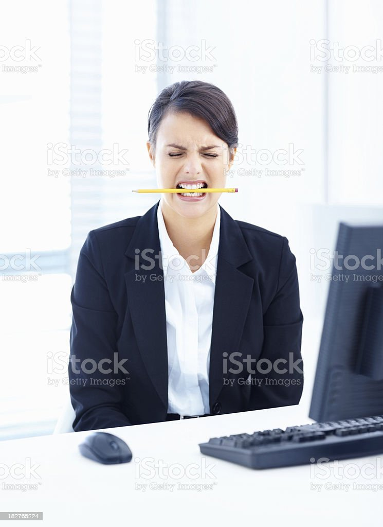 Business woman biting a pencil in frustration at work royalty-free stock photo
