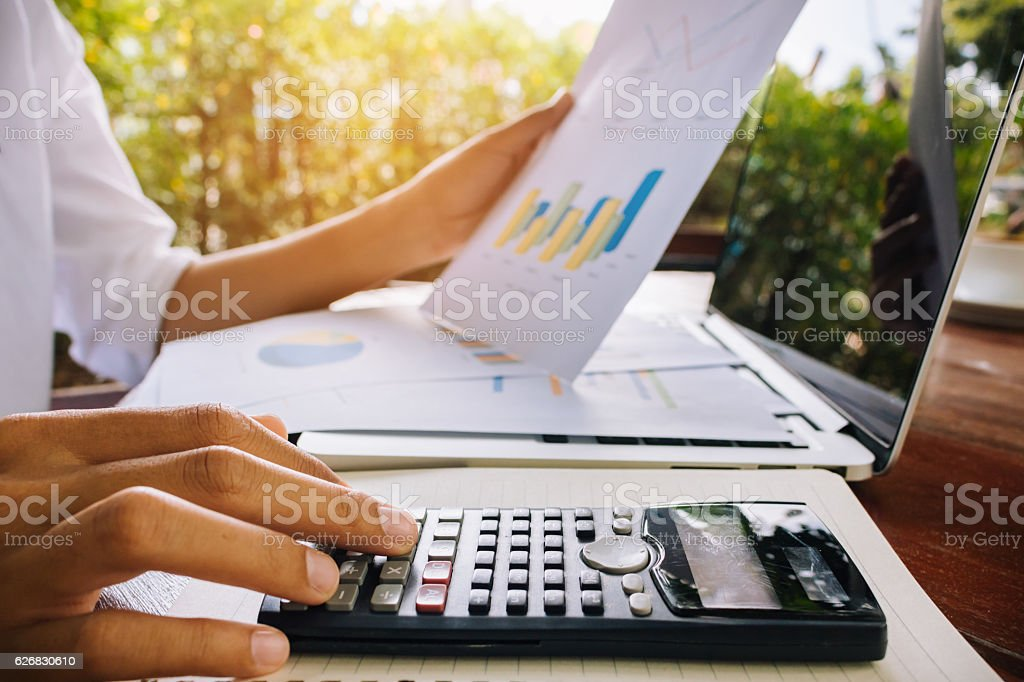 business woman calculate and analyzing graph document financial. stock photo