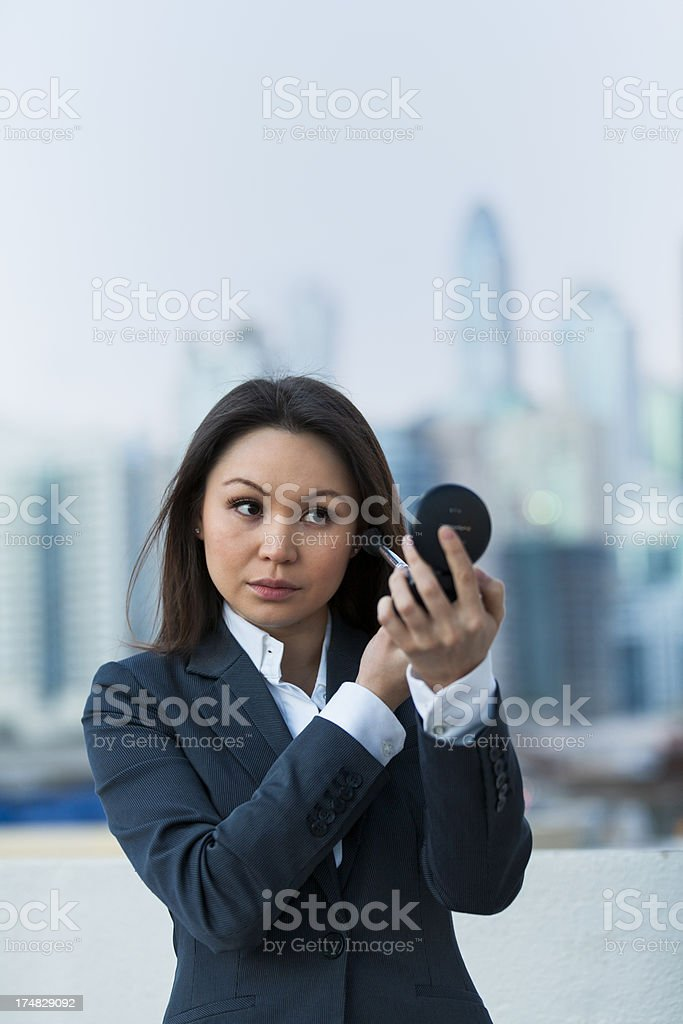 Business woman checking her make-up stock photo