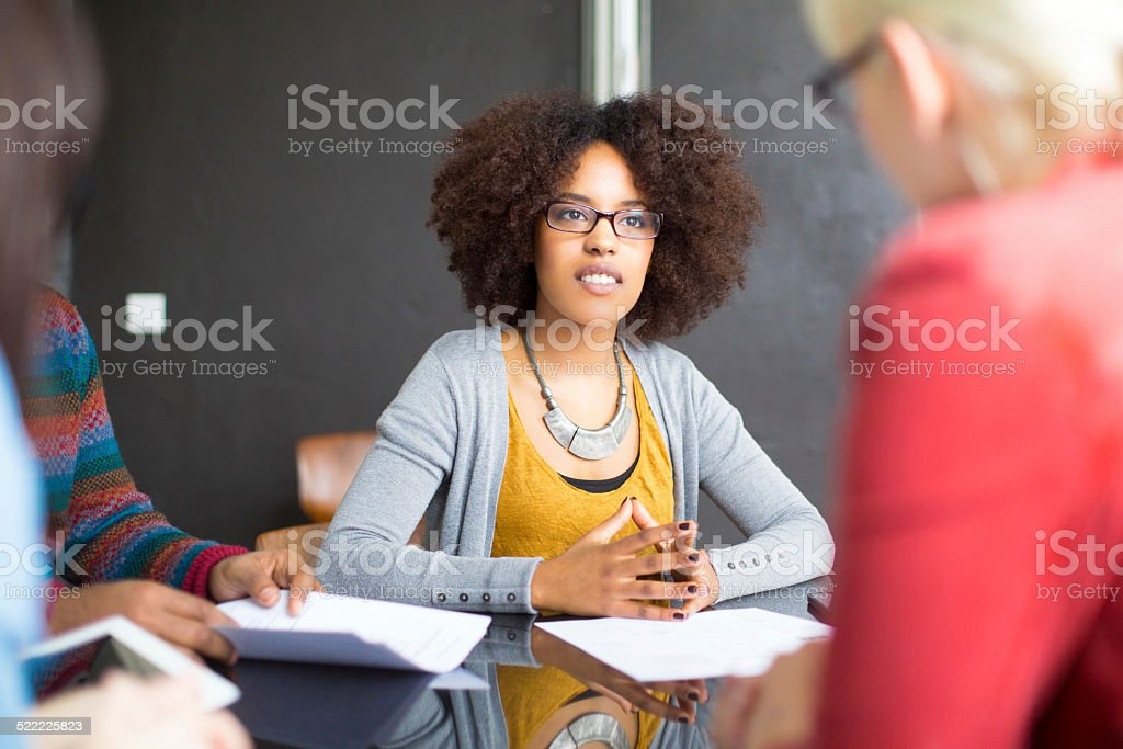 Business woman discussing profits with her colleagues stock photo