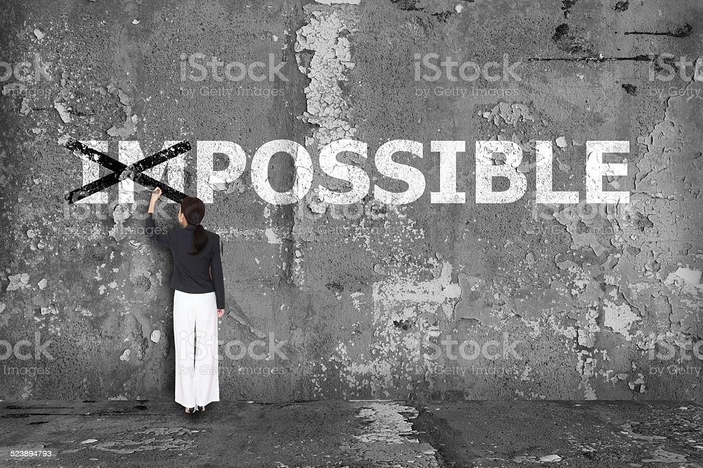 business woman drawing possible on wall stock photo