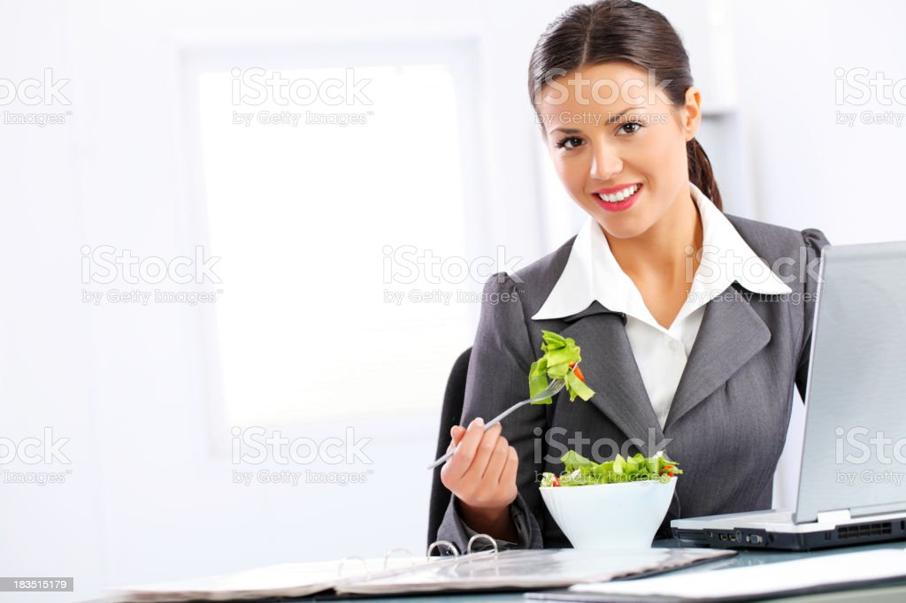 Business woman eating vegetable salad, sitting on workplace. royalty-free stock photo