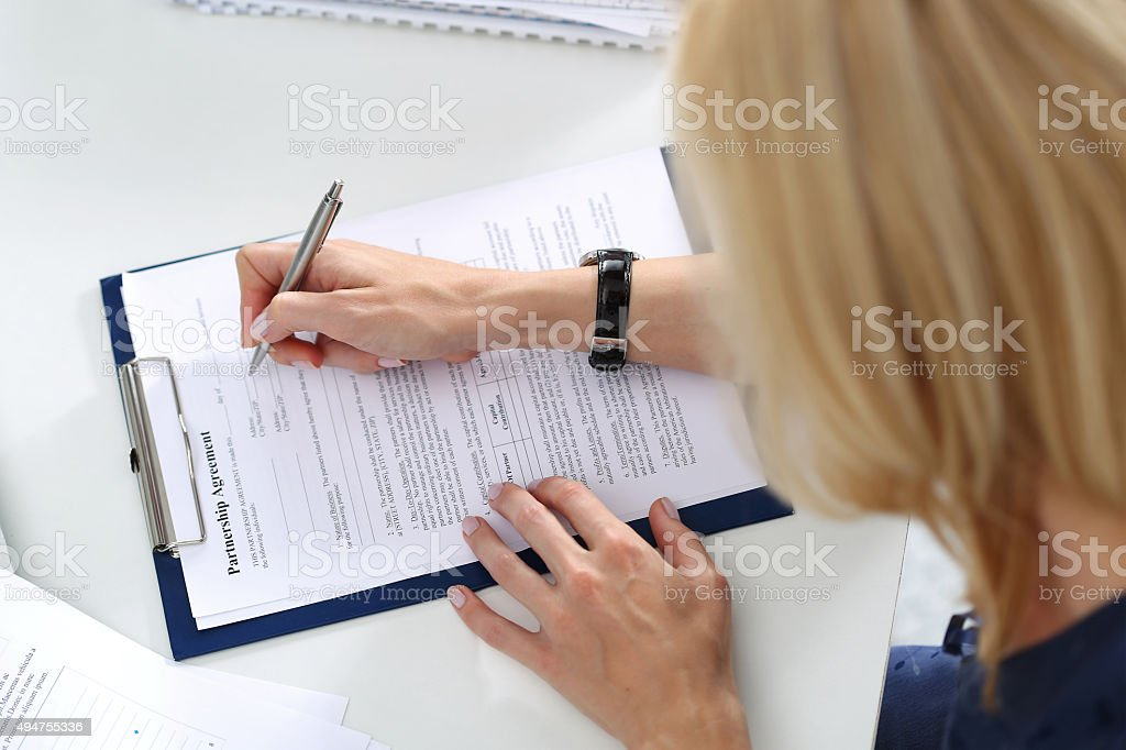 Business woman filling partnership agreement blank stock photo