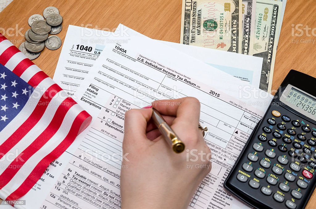Business woman fills tax form with money, pen, flag,  calculator stock photo